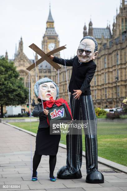 Campaigners from Avaaz dressed as British Prime Minister Theresa May and Australian media Mogul Rupert Murdoch pose during a photocall outside the...