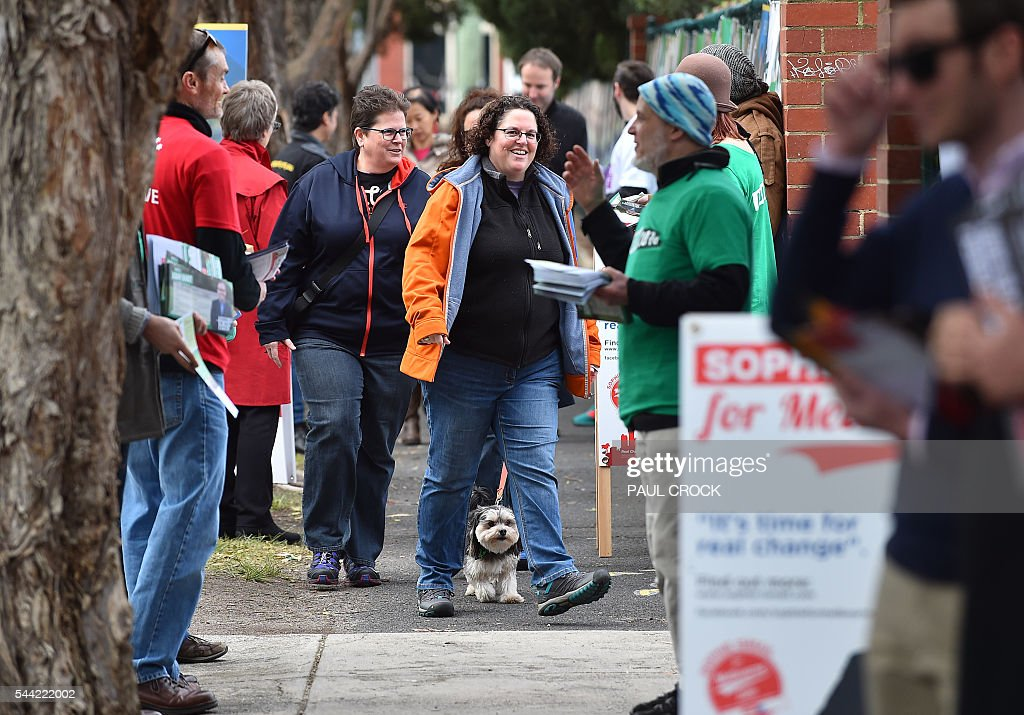 Campaigners hand out 'how to vote' cards as people arrive to cast their vote in the Australian Federal Election in Melbourne on July 2, 2016. Australia is voting in a general election which is expected to be a close race between the ruling Liberal-National coalition and the opposition Labor Party. / AFP / Paul Crock