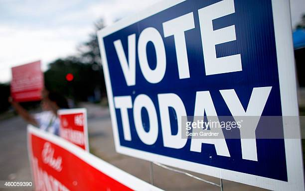 Campaigners parade along the sidewalks as people head to their polling stations to vote in today's runoff Senate election between incumbent US Sen...