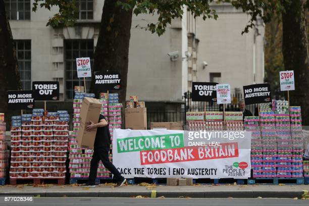 Campaigners protest against government austerity programmes next to crates of tinned food destined for food banks outside Downing street in central...