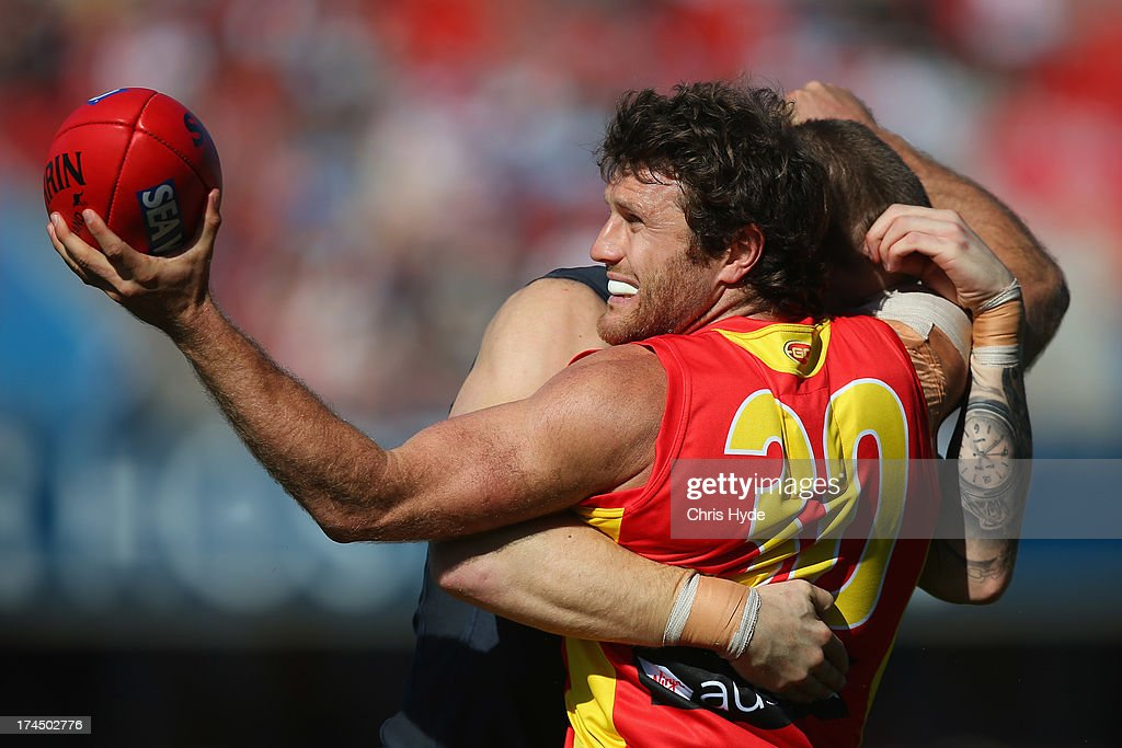 Campbell Brown of the Suns is tackled by Mitch Robinson of the Blues during the round 18 AFL match between the Gold Coast Suns and the Carlton Blues at Metricon Stadium on July 27, 2013 in Gold Coast, Australia.