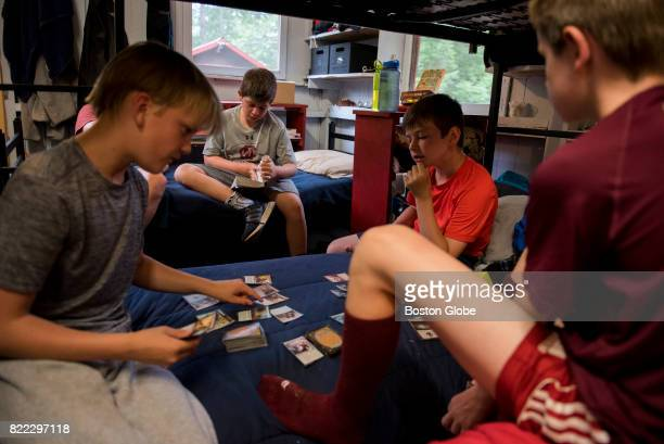 Camper Carson Krulewitch center reads 'The Mark of Athena' while his fellow campers play Magic the Gathering during a rainy afternoon at Camp...