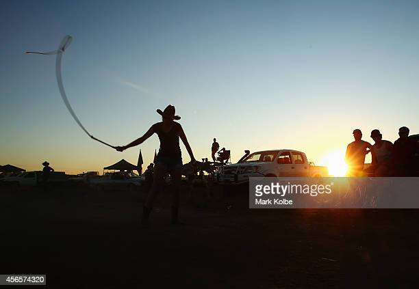 A camper cracks a whip as others watch on in the 'Ute Paddock' on the first day of the 2014 Deni Ute Muster at the Play on the Plains Festival...