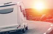 Camper RV Sunset Trip. Motorhome Summer Journey. Class C Recreational Vehicle on the Road