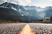 RV camper stands on side of road on background of huge mountain. Friends travel to motorhome on mountain road. Travelers rest on sidelines and enjoy mountain view