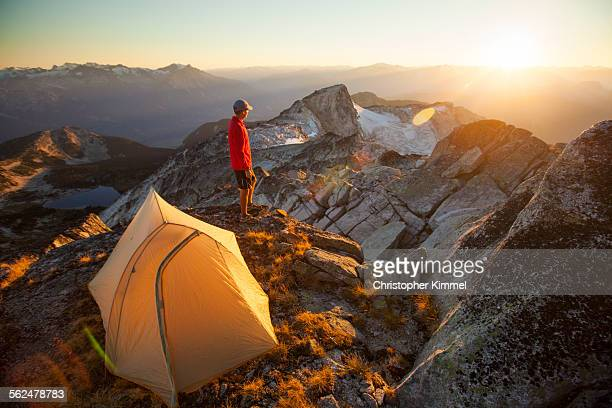 A camper watches the sunset while standing beside his tent on the summit of Saxifrage Peak.