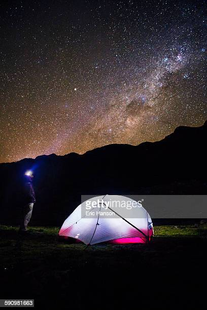 Camper with Illuminated Tent Gazes at Stars
