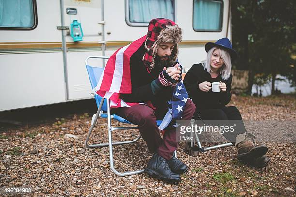 Campers holding steel mugs warming up near fire