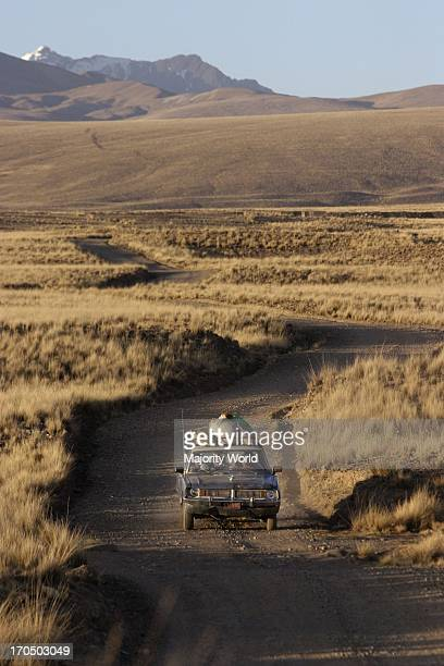 A campesino family riding on a car in a dirt road in the Altiplano region of Bolivia behind a snow covered mountain Tuna Condoriri Altiplano La Paz...