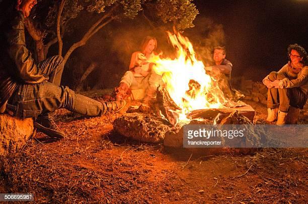 Fuoco di accampamento di amici in cerchio sulla fuoco