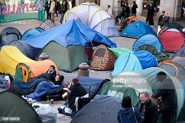 Camping activists slowly waking up under a giant tarpaulin beside the main entrance to the cathedral Day three of the occupation and the first Monday...