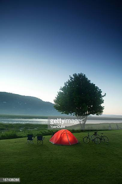 camping tent nearby river and mountain at dusk