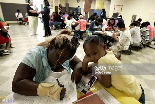 Camry Thomas sixyearsold watches as her mother Candace Thomas completes registration forms at Joseph A Craig Elementary School March 29 2006 in New...
