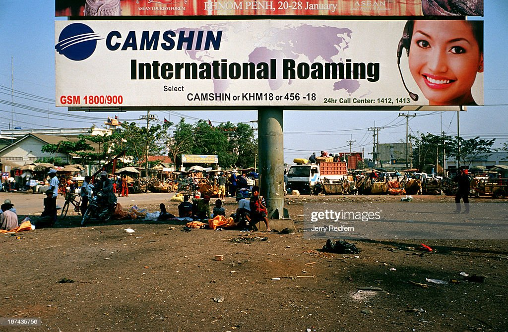 A Camshin telephone sign hangs over a filthy park, promoting the International Roaming features of the mobile phone service, in Poipet..