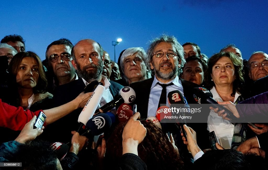Can Dundar (2nd R), editor-in-chief of the newspaper Cumhuriyet, speaks to the media as Erdem Gul (2nd L), the papers Ankara bureau chief, and Dundar's wife Dilek Dundar stand next to him outside the Istanbul's Caglayan courthouse after the court announced its decision in Istanbul, Turkey on May 06, 2016. A high court in Istanbul convicted Turkish journalists Can Dundar and Erdem Gul Friday night on charges of revealing state secrets, sentencing them to five years and 10 months, and five years in prison, respectively.