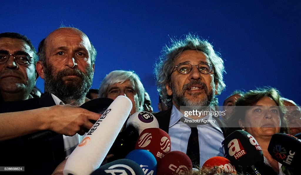 Can Dundar (2nd R), editor-in-chief of the newspaper Cumhuriyet, speaks to the media as Erdem Gul (2nd L), the papers Ankara bureau chief, and Dundar's wife Dilek Dundar (R) stand next to him outside the Istanbul's Caglayan courthouse after the court announced its decision in Istanbul, Turkey on May 06, 2016. A high court in Istanbul convicted Turkish journalists Can Dundar and Erdem Gul Friday night on charges of revealing state secrets, sentencing them to five years and 10 months, and five years in prison, respectively.