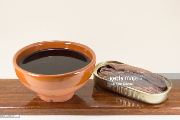 can of  anchovies  in olive oil and an earthenware cup of red wine