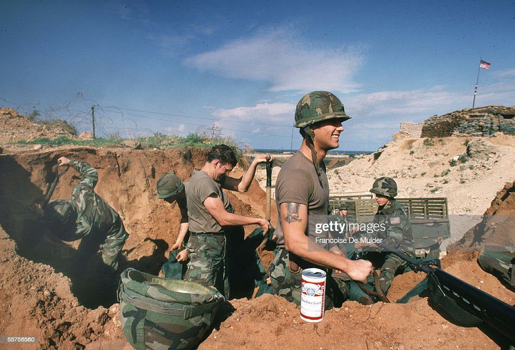 A can of beer sits in the sand next to a group of United States Marines who dig up material to fill sandbags during the failed Multinational Force peacekeeping intervention in the Lebanese Civil War, Beirut, September 1983. FDM