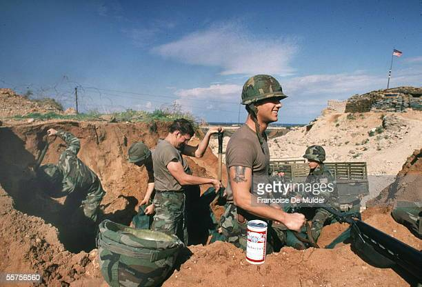 A can of beer sits in the sand next to a group of United States Marines who dig up material to fill sandbags during the failed Multinational Force...
