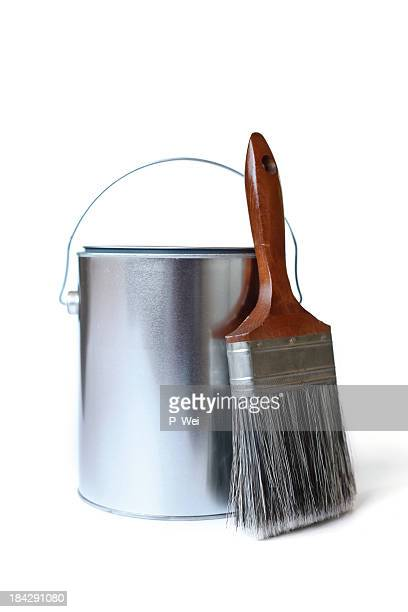 Can of paint with paint brush against white background