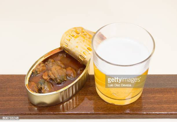 can of  small scallops in vieira sauce and glass of beer