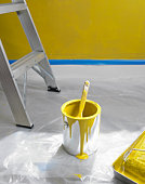 Can of yellow paint and ladder on floor