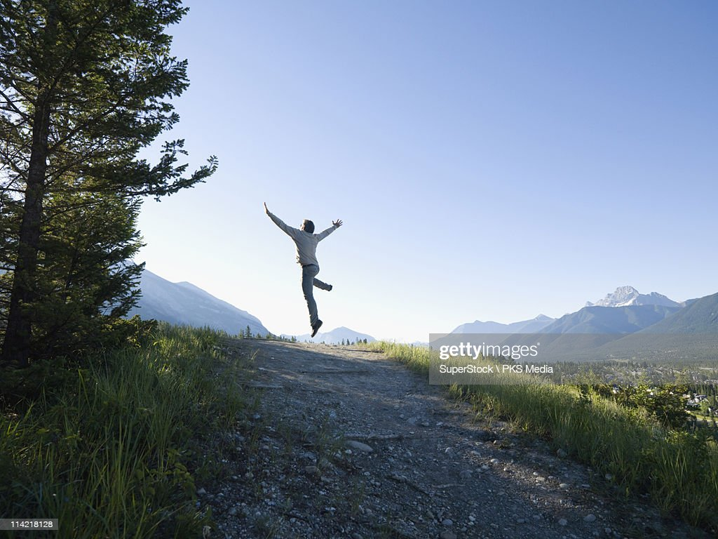 Canada, Alberta, Canmore, Rear view of man jumping above mountain trail : Stock Photo