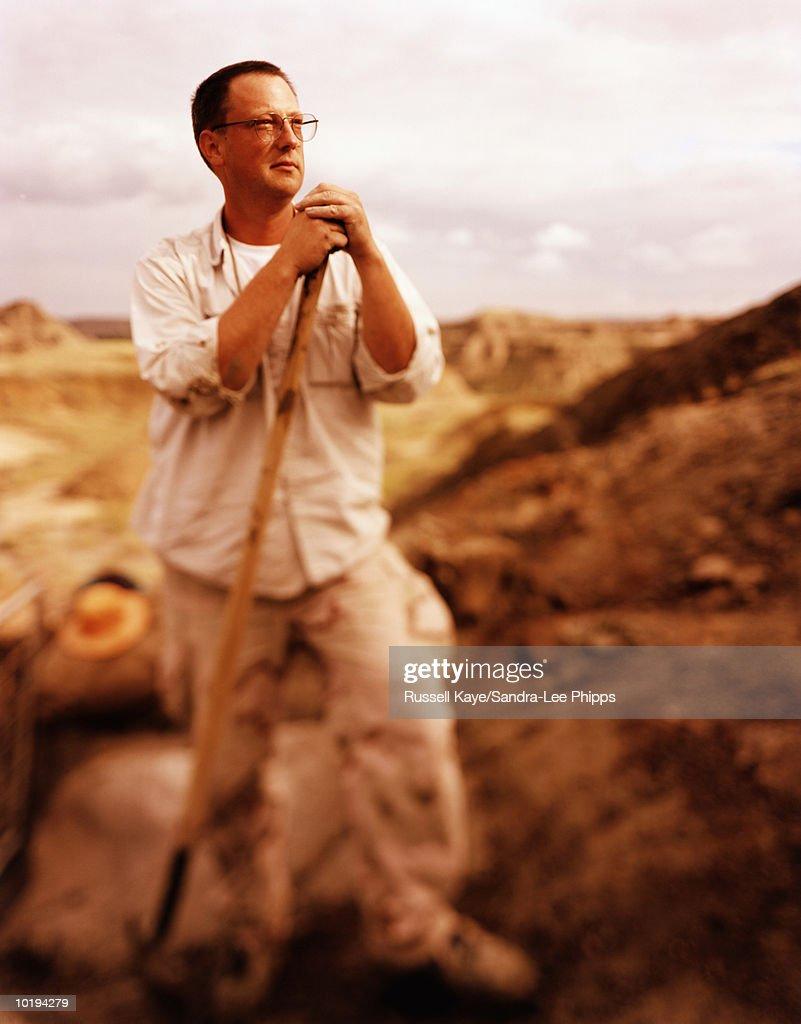 Canada, Alberta, Dinosaur Provincial Park, man holding shovel : Stock Photo