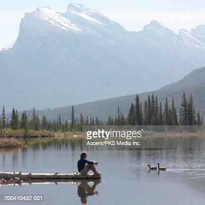 Canada, Alberta, man on log watching Canada geese swimming on lake : Stock Photo