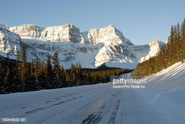 Canada, Banff National Park, snow covered path, mountain peaks in background