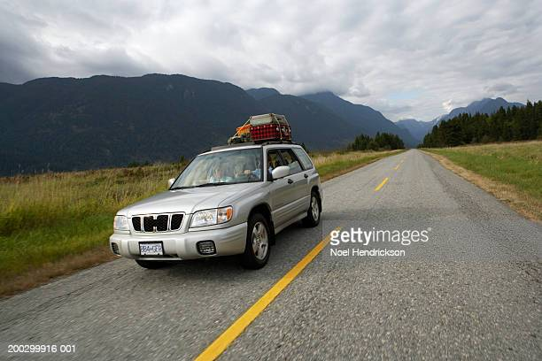 Canada, British Columbia, Pitt Meadows, couple driving sports utility vehicle on rural road