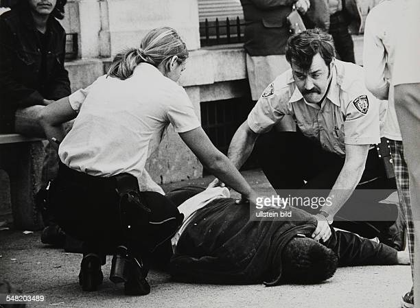 Canada British Columbia Vancouver Two policemen caring for an Indian who is dying of alcoholic poisoning