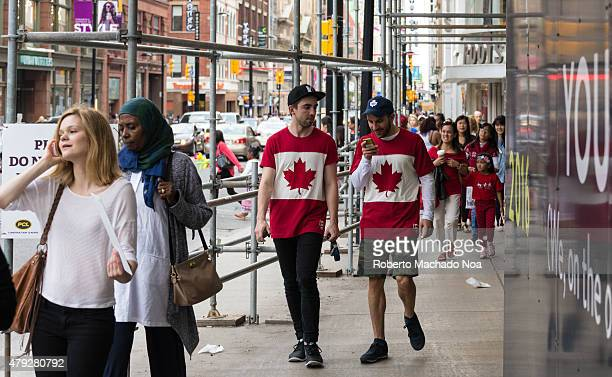 SQUARE TORONTO ONTARIO CANADA Canada Day celebrations in Toronto Multicultural people in the street and two young men wearing the Canadian Flag on...