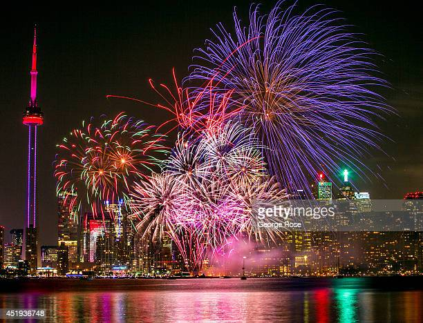 Canada Day fireworks display is viewed from Centre Island in Toronto Harbour looking back at the downtown skyline on July 1 2014 in Toronto Ontario...