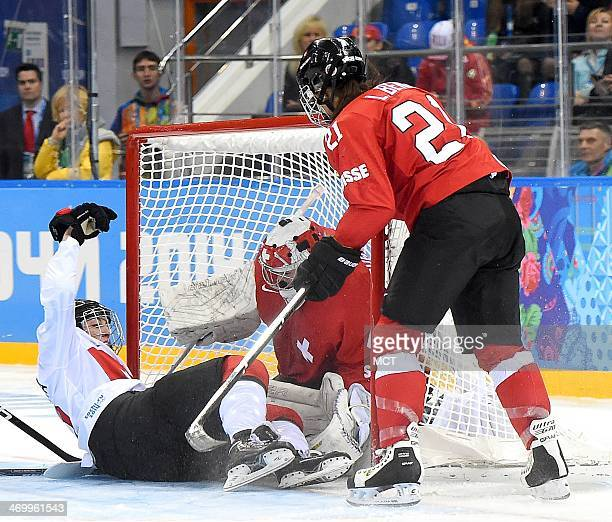 Canada forward Meghan AgostaMarciano crashes into Switzerland goalie Florence Schelling during the third period in a women's hockey game at the...
