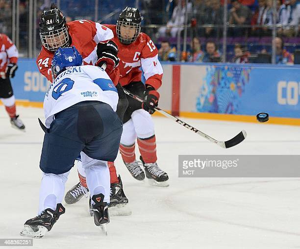 Canada forward Natalie Spooner fires a shot against Finland defenseman Jenni Hiirikoski in the first period of a Winter Olympics women's hockey game...