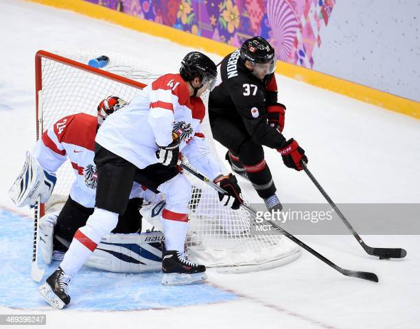 Canada forward Patrice Bergeron tries to get off a shot from behind the goal but is defended by Austria defenseman Mario Altmann during the third...