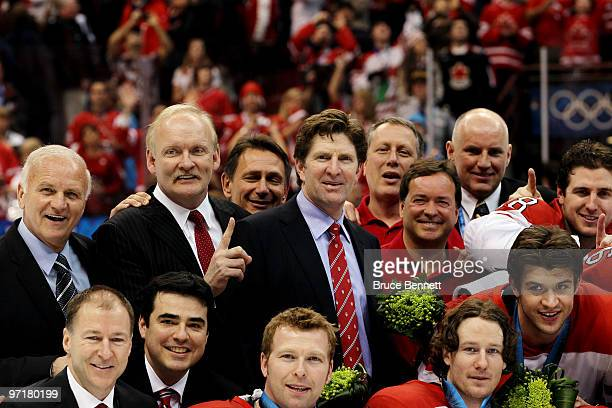 Canada head coach Mike Babcock celebrates with fellow coaches and players after winning gold during the ice hockey men's gold medal game between USA...