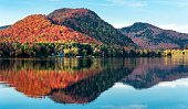 The hills covered with red maple forests are reflected in a lake in Quebec on a beautiful autumn evening