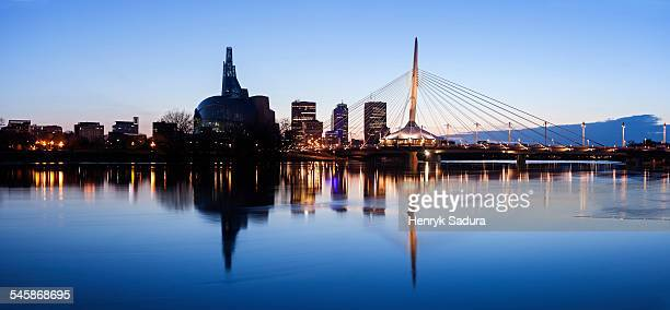 Canada, Manitoba, Winnipeg, Illuminated skyline reflecting in calm Assiniboine River