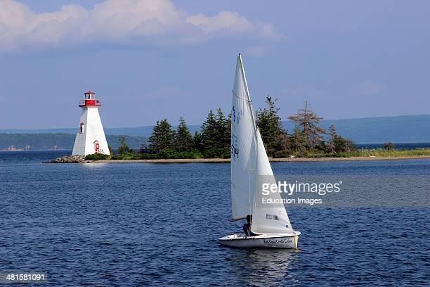 Canada Nova Scotia Cape Breton Baddeck Bras dOr Lake lighthouse with sloop sail boat