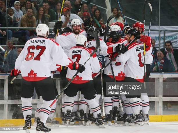 Canada players celebrate winning the series after a sudden death goal by Adam Cracknell during the Ice Hockey Classic match between the United States...