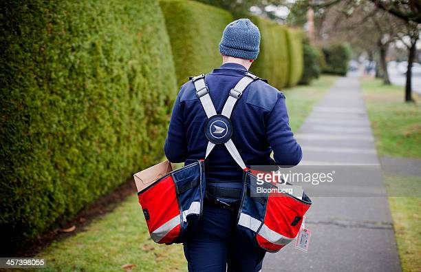 A Canada Post letter carrier delivers mail by foot to houses in Vancouver British Columbia Canada on Monday Dec 16 2013 Canada Post announced that it...