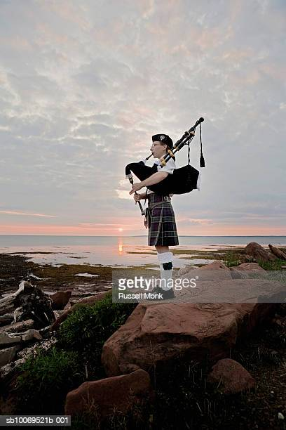 Canada, Prince Edward Island, Point Prim, woman playing bagpipes on shore