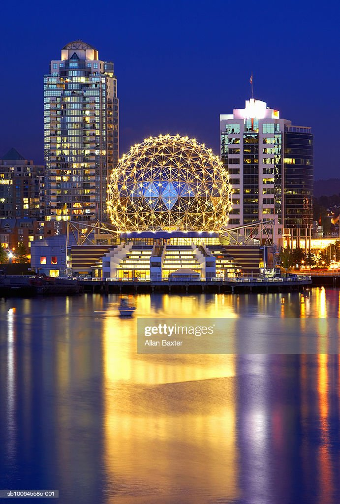 Canada, Vancouver, illuminated Telusphere at Science centre reflecting in water : Stock Photo