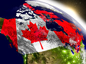 Canada with embedded flag on planet surface during sunrise. 3D illustration with highly detailed realistic planet surface and visible city lights. 3D model of planet created and rendered in Cheetah3D