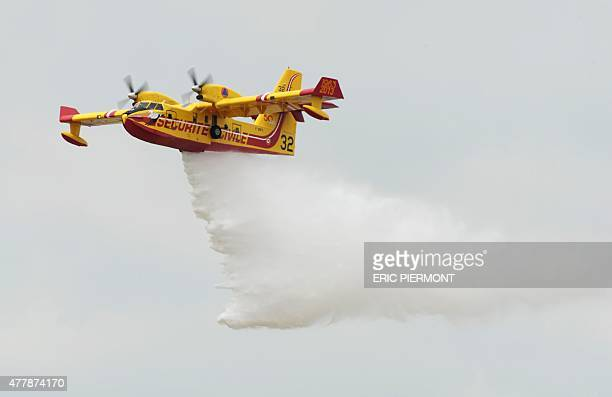 A Canadair CL415 drops water as it performs a flying display during the public days of the 51st International Paris Air Show in Le Bourget north of...