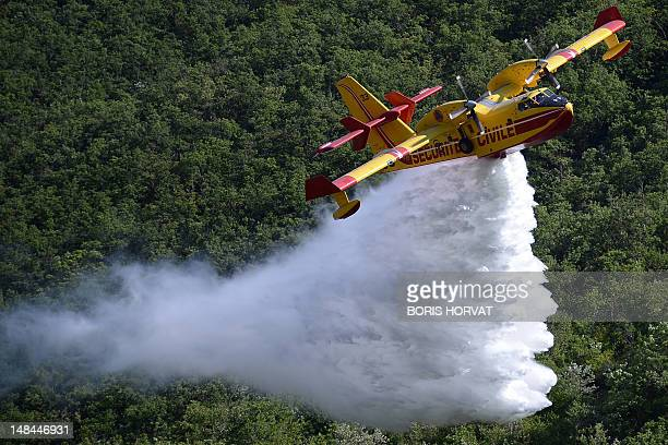 A Canadair drops water on a forest during a presentation on a forest fire on July 16 2012 in DignelesBains southern France as French Interior...
