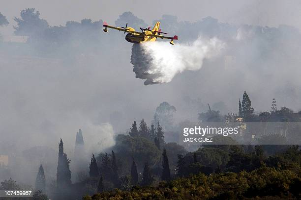 A Canadair firefighter plane sprays its load of water over flames in the village of Ein Hod on December 4 2010 as the massive fire ripping through...