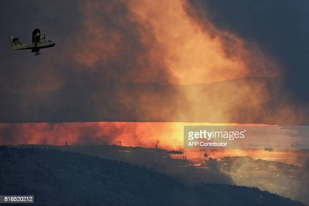 Canadair of the Croatian Air Force flies over the village of Gornje Sitno near the Adriatic coastal town of Split during a fire on July 17 2017...